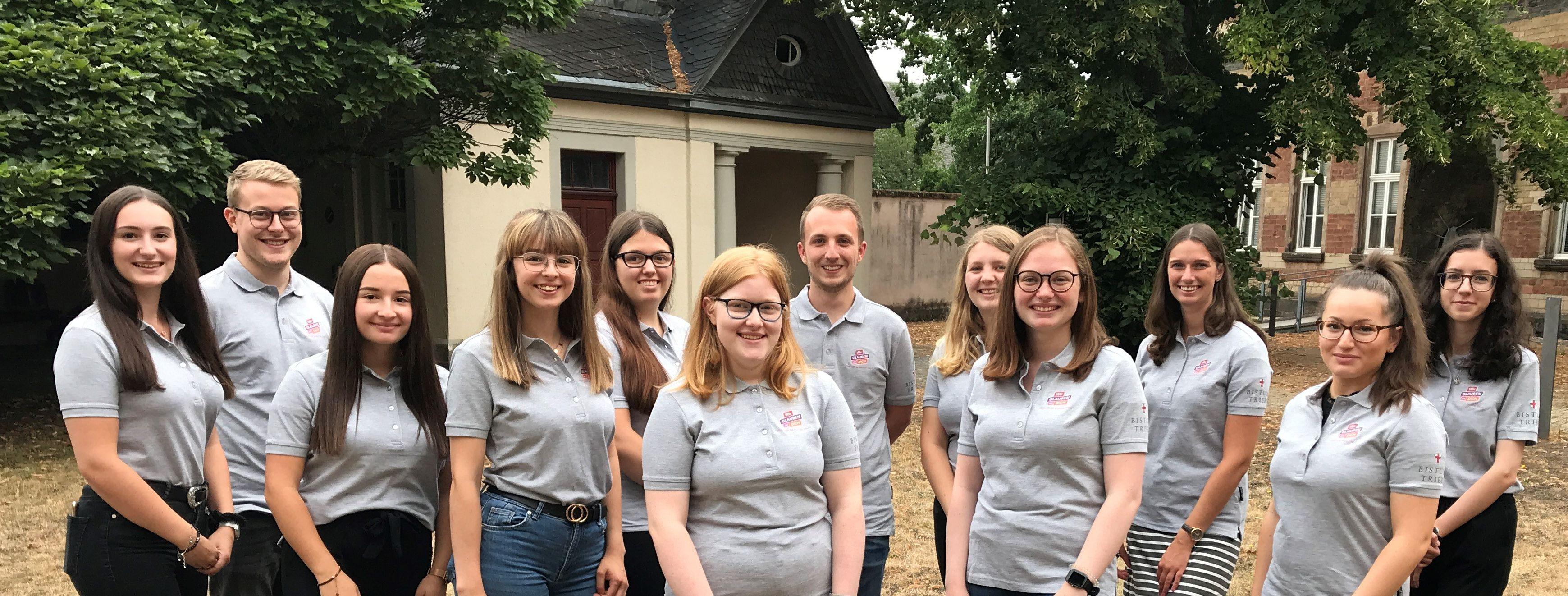 12 Mädchen und Jungen stehen im Garten des BIschöflichen Generalvikariats als Gruppe zusammen und lächeln in die Kamera.