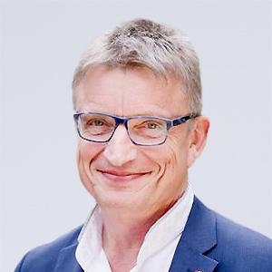 Ein Herr mit Brille und Anzug lächelt in die Kamera.