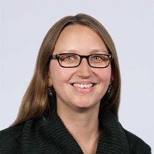Eine junge Frau mit langen braunen Haaren und Brille schaut lächelnd in die Kamera.