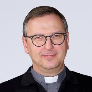 Ein Herr in Priesterkleidung schaut freundlich in die Kamera.