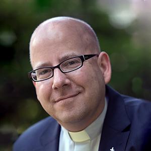 Ein Mann in Priesterkleidung lächelt in die Kamera.