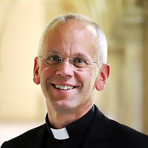 Ein Herr in Priesterkleidung schaut lächelnd in die Kamera.