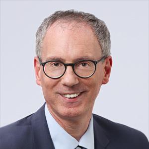 Ein Herr mit Brille lächelt in die Kamera.
