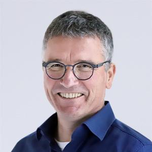 Ein Herr mit Brille schaut lächelnd in die Kamera.