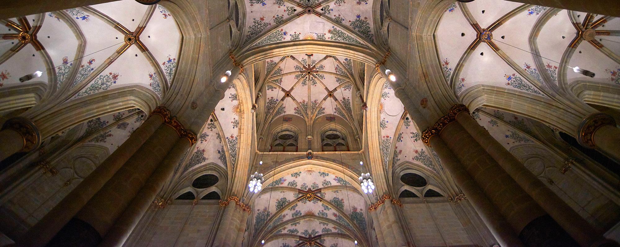 Ein hell erleuchtetes Deckengewölbe einer Kirche mit blauen Ornamenten und roten Ausläufern.