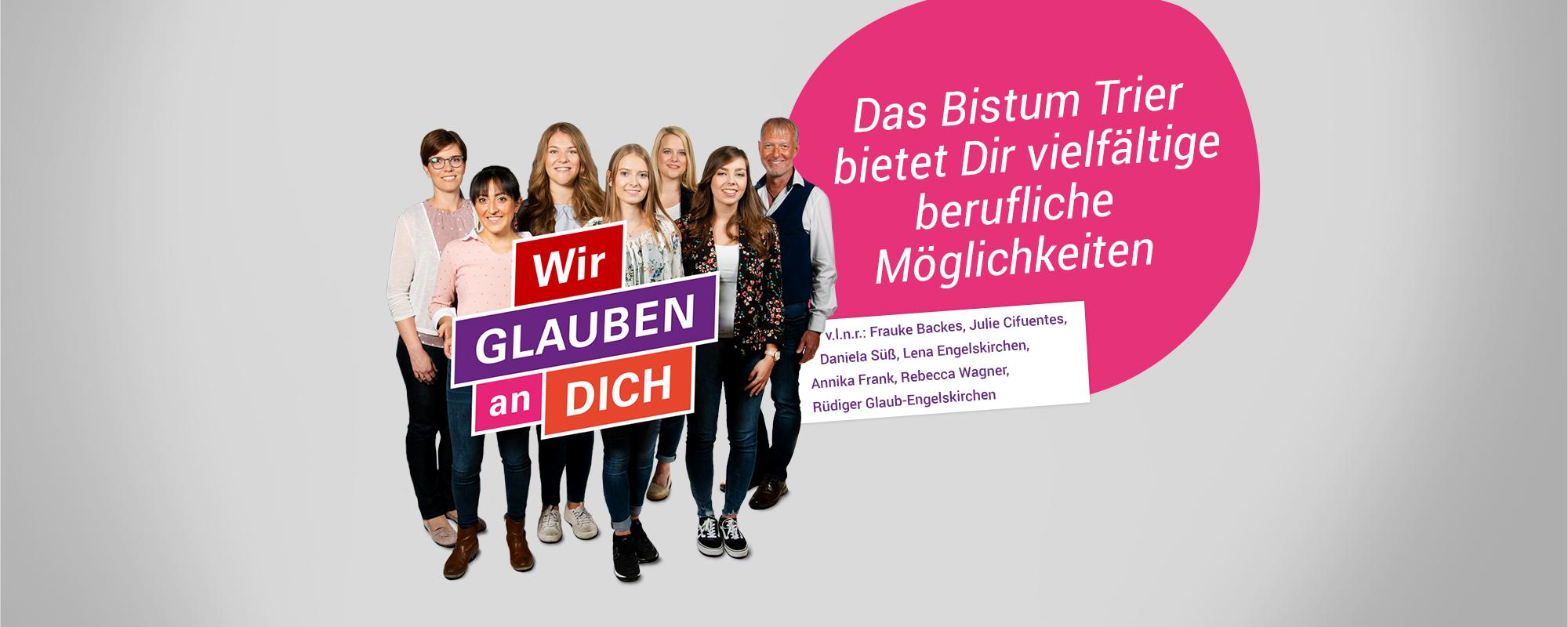 7 Personen stehen in 2 Reihen nebeneinander zum Gruppenfoto. Sie lächeln und halten das Schild Wir Glauben an Dich in die Kamera.