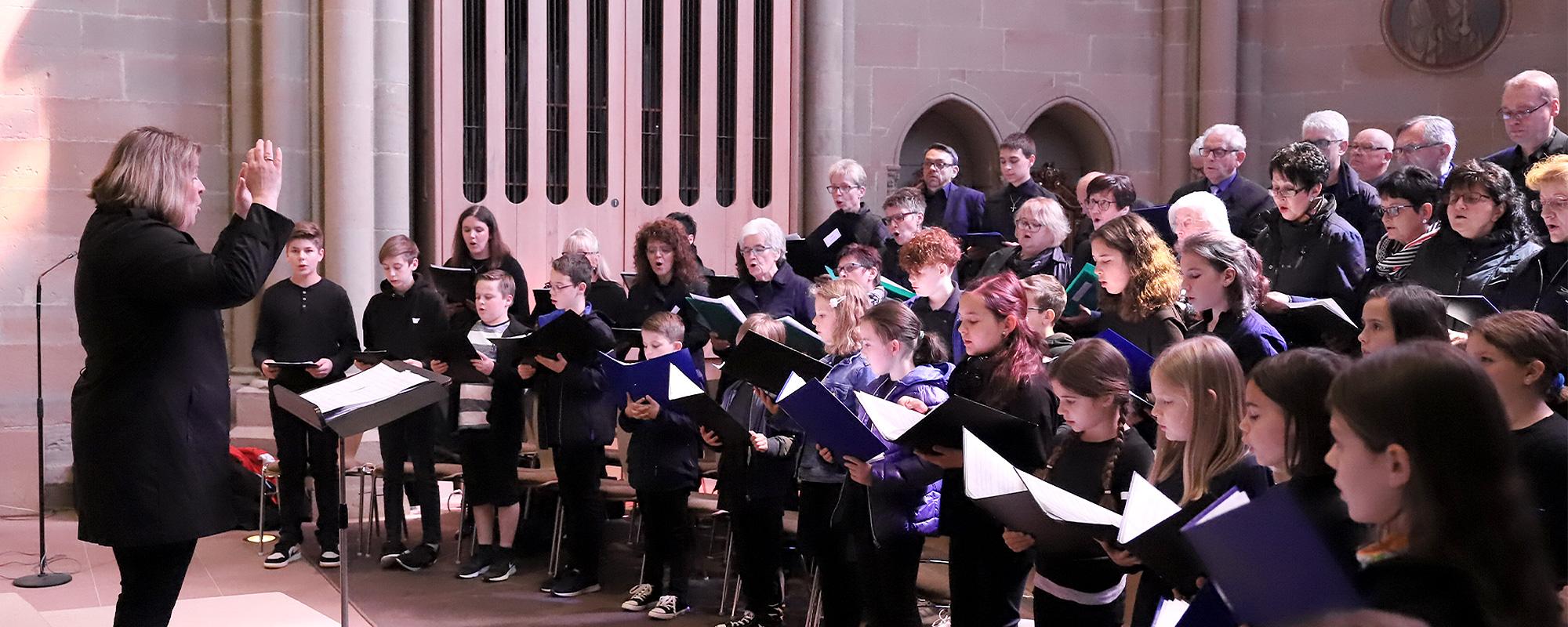 Gemischter Chor allen Alters singt im Altarraum einer Kirche. Sie tragen schwarze Kleidung, allerdings nicht einheitlich und werden von einer Frau dirigiert.