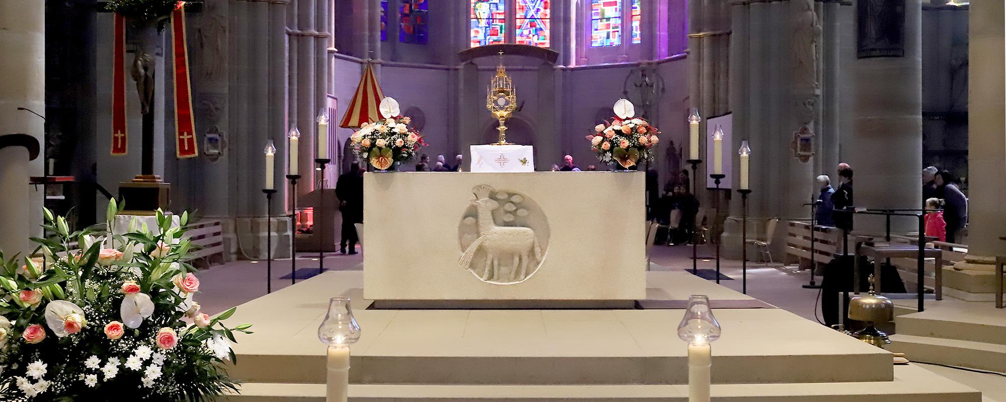 Ein hergerichteter Altar mit Blumengestecken rechts und links sowie links vor dem Altar auf dem Boden.