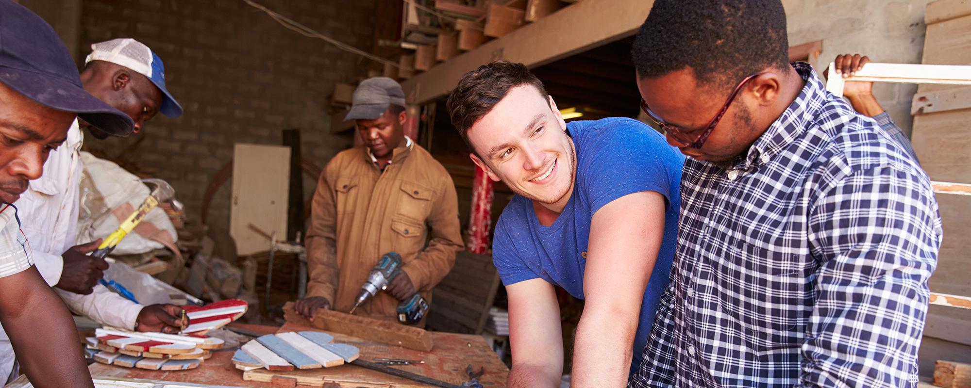 4 dunkelhäutige Menschen arbeiten mit einem hellheutigen jungen Mann in einer Werkstatt. Sie haben Herzen aus Holz gefertigt.
