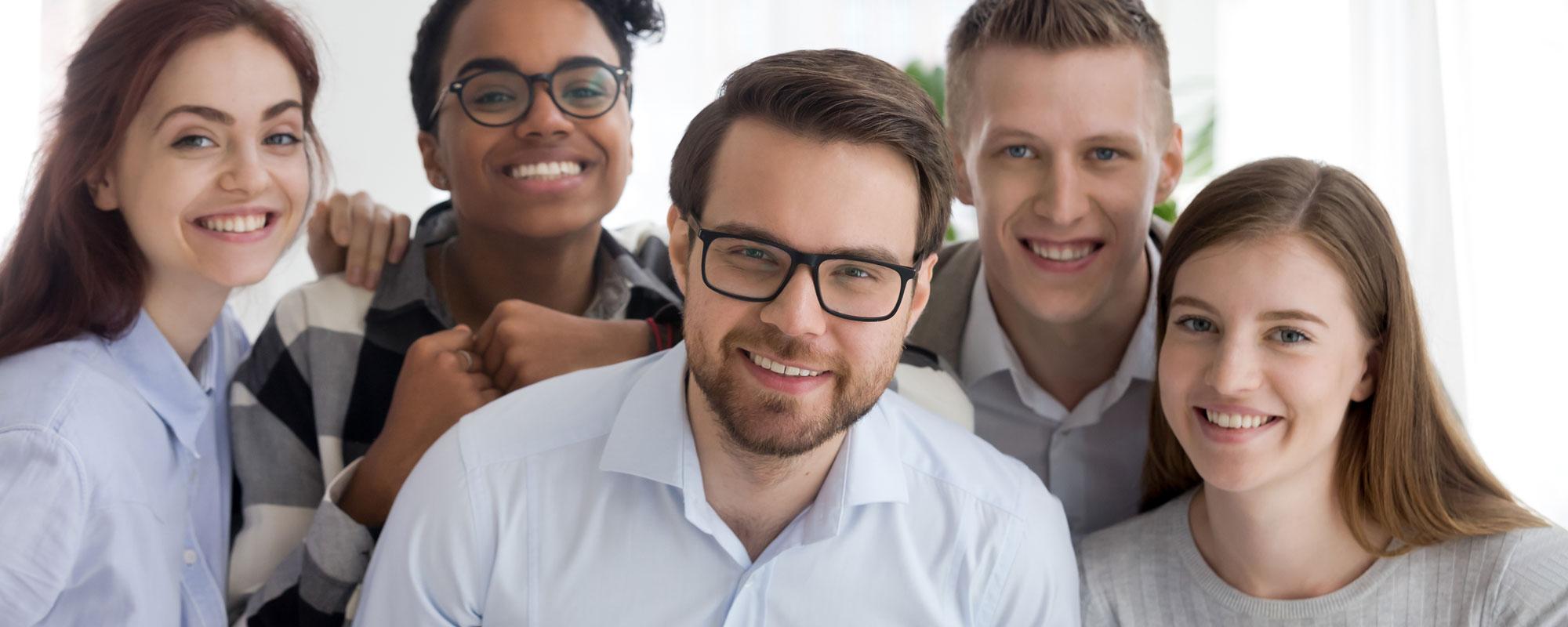 3 junge Männer und 2 Frauen stehen eng zusammen und lächeln in die Kamera.