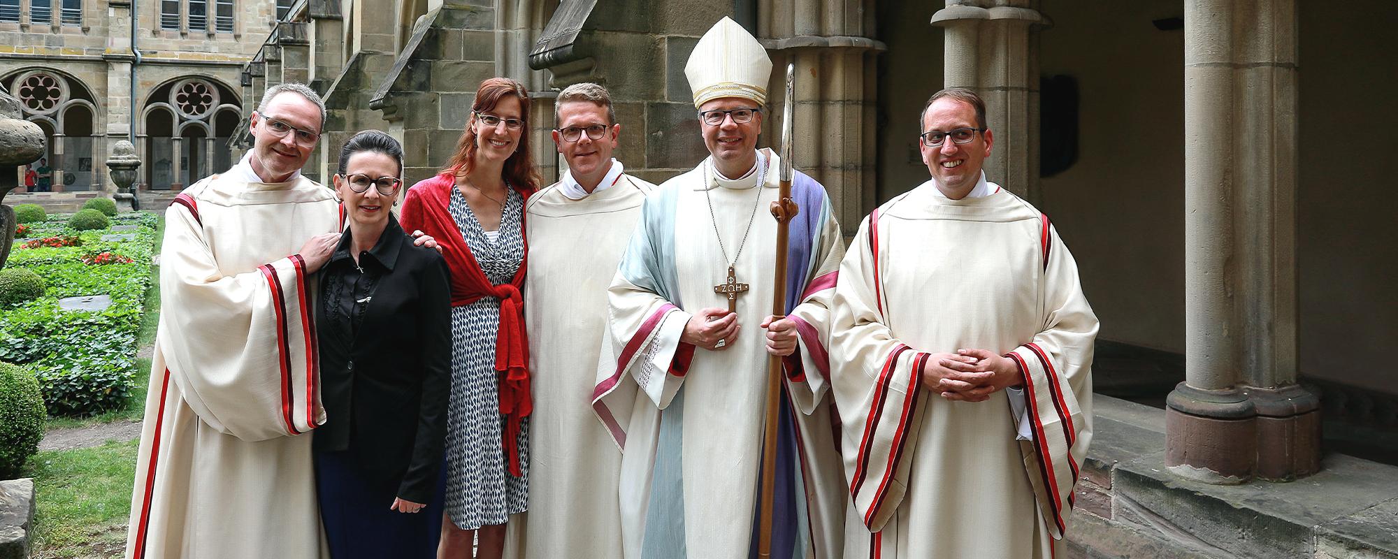 Bischof Dr. Stefan Ackermann steht mit 3 neugeweihten Diakonen und deren Ehefrauen im Kreuzgang zum Gruppenfoto zusammen.