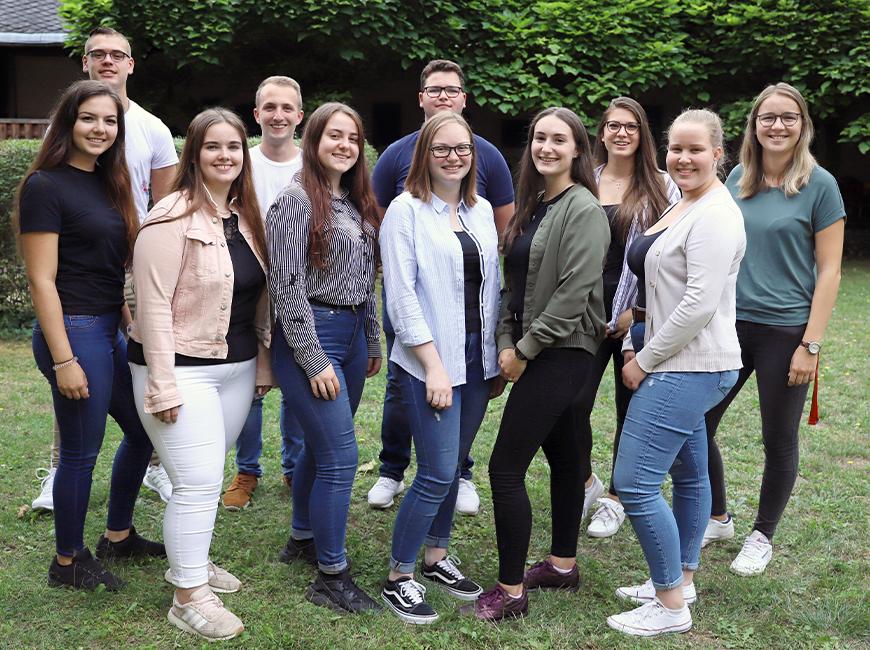 11 junge Leute stehen im Garten des Generalvikariats zu einem Gruppenfoto zusammen. Es sind 8 Mädchen und 3 Jungen in legeren Outfits..