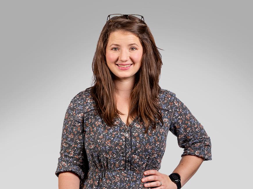 Ein Mann und eine Frau schauen lächelnd in die Kamera, sie stehen nebeneinander und die Frau stemmt die rechte Hand in die Hüfte