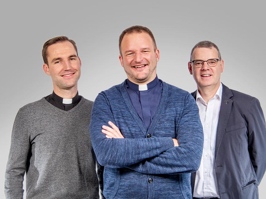 3 Priester blicken lächelnd in die Kamera, sie stehen locker in einer Dreiergruppe